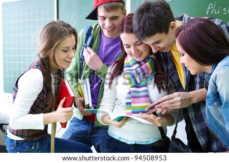 Group of students discussing in classroom - stock photo