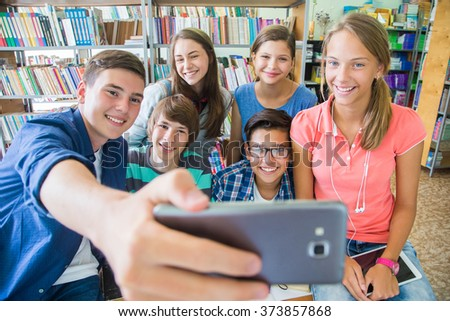 Group of students doing selfie in the classroom at school - stock photo