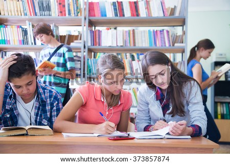 group of students engaged in learning at the desk in the library - stock photo