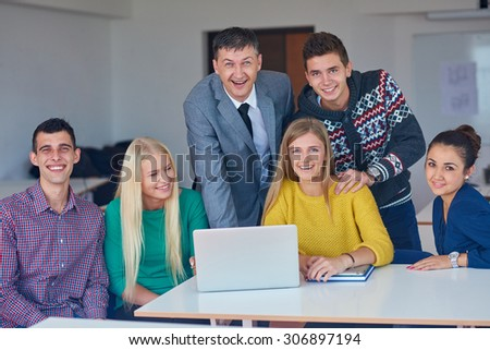 group of students getting suppport from teacher and working on laptop computer at tach classroom