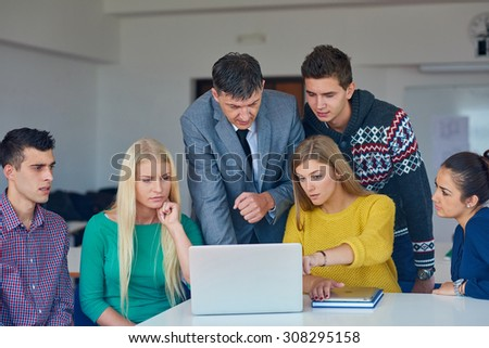 group of students getting suppport from teacher and working on laptop computer at tach classroom - stock photo