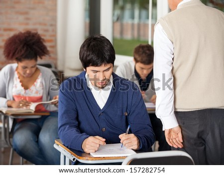 Group of students giving exam while teacher supervising them in classroom - stock photo