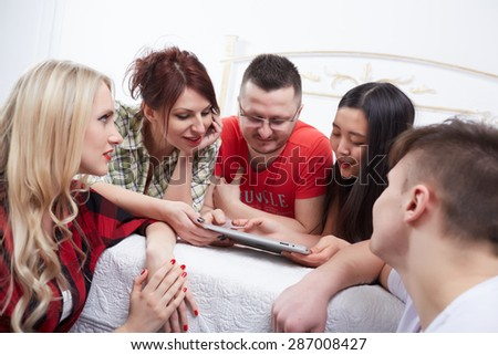 group of students in a bright room on the bed watching something on a tablet