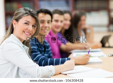 Group of students in class taking notes - stock photo