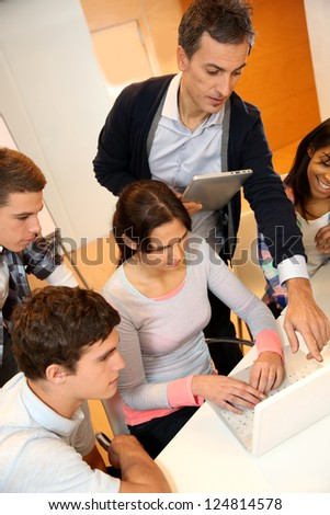 Group of students in computer training with teacher - stock photo