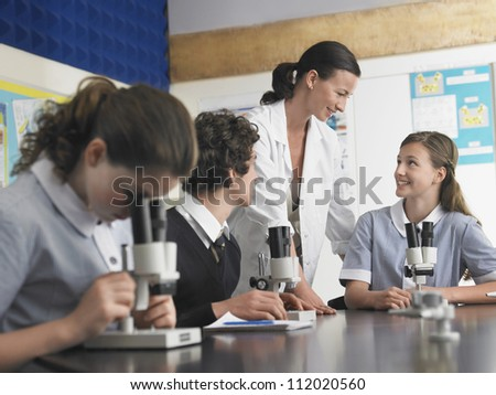 Group of students in discussion with teacher in laboratory - stock photo