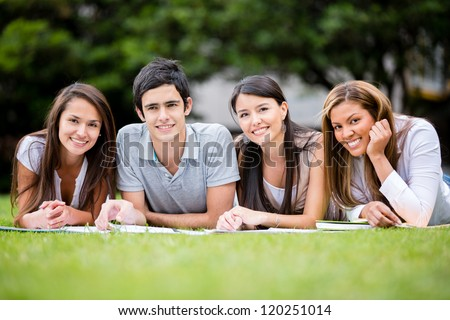 Group of students outdoors lying on the floor and smiling