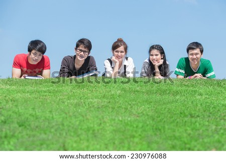 Group of students outdoors lying on the floor and smiling - stock photo