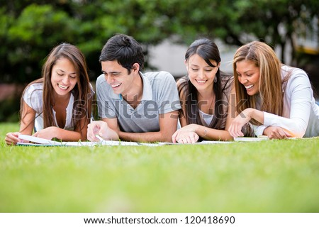 Group of students outdoors studying and looking happy - stock photo