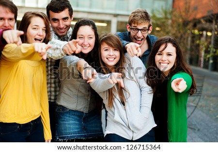 Group of students outside pointing and smiling - stock photo