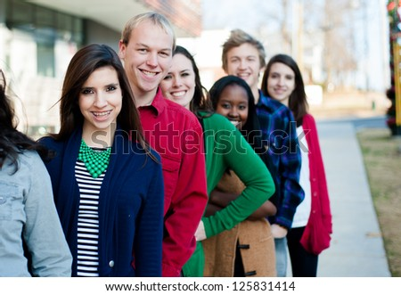 Group of students outside smiling in a line - stock photo