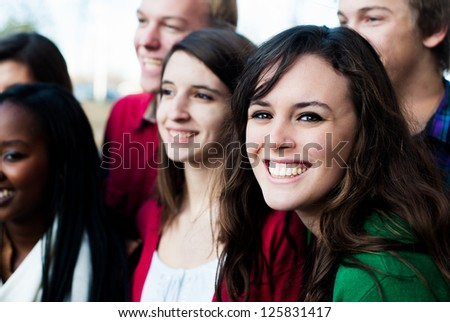 Group of students outside smiling with focus on one