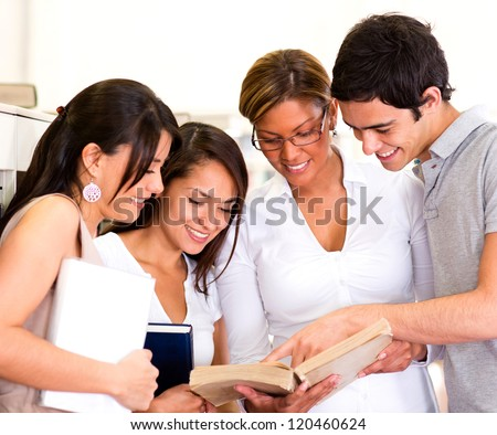 Group of students reading a book at the library - stock photo