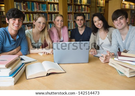 Group of students sitting at a table in a library while using the laptop and learning