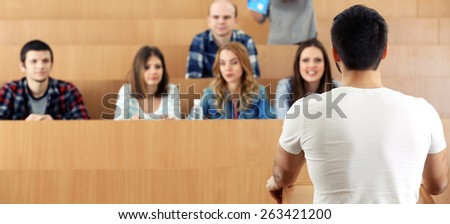 Group of students sitting in classroom and listening speaker - stock photo