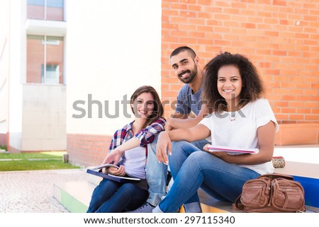 Group of students sitting on school stairs - stock photo