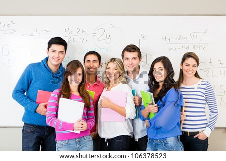 Group of students smiling and holding notebooks