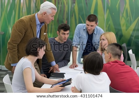 group of students study with professor in modern school classroom