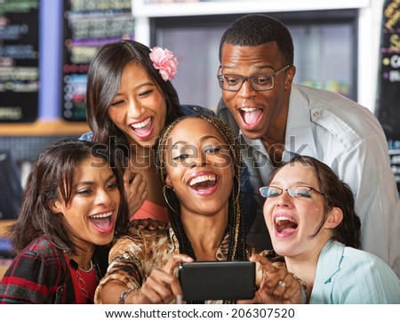 Group of students taking self-portrait with camera phone - stock photo