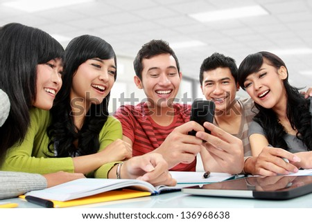 Group of students using mobile phone together - stock photo