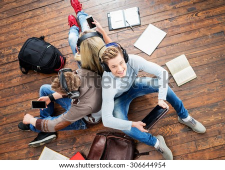 Group of students using smartphones and tablet in headphones listening to the music and leaning on each other on wooden floor having notebooks and bags around them.   - stock photo