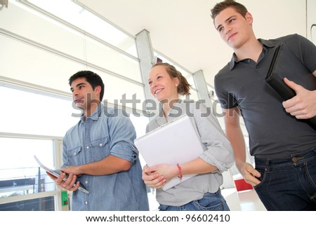Group of students walking in school hallway - stock photo