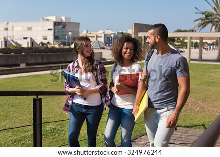 Group of students walking on school campus - stock photo