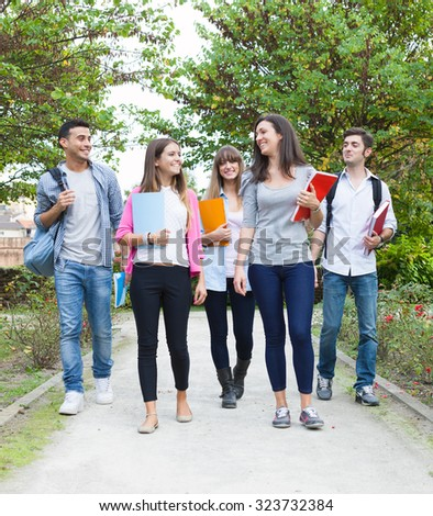 Group of students walking outdoors - stock photo