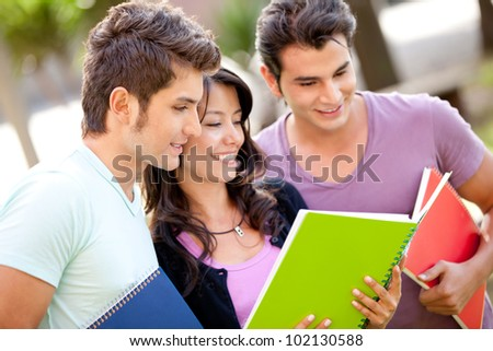 Group of students with notebooks smiling outdoors - stock photo