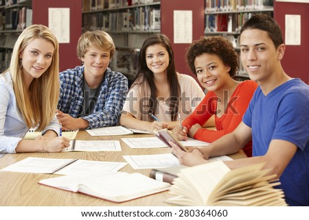 Group of students working together in library - stock photo