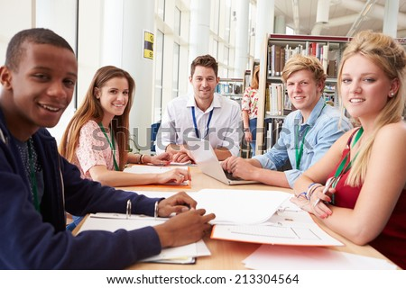 Group Of Students Working Together In Library With Teacher - stock photo
