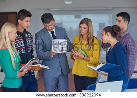 group of students working with teacher on wooden small house model - stock photo