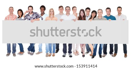 Group of stylish professional business people standing in a line holding up a long blank banner for your advertising or text - stock photo