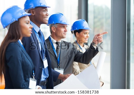group of successful architects discussing project in modern office - stock photo