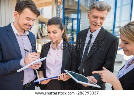 Group of successful business people in suits discussing business strategy.