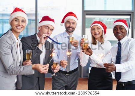 Group of successful colleagues in Santa caps having Christmas party in office - stock photo
