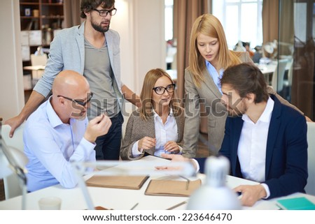 Group of successful designers sharing ideas and discussing them - stock photo