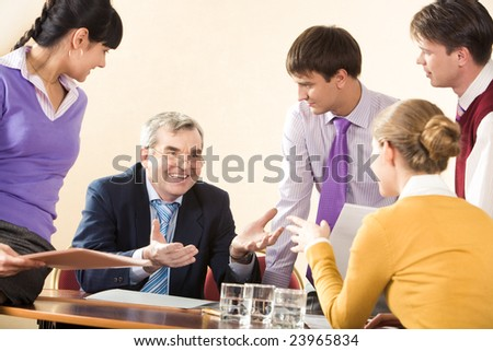 Group of successful managers communicating with senior boss at meeting - stock photo