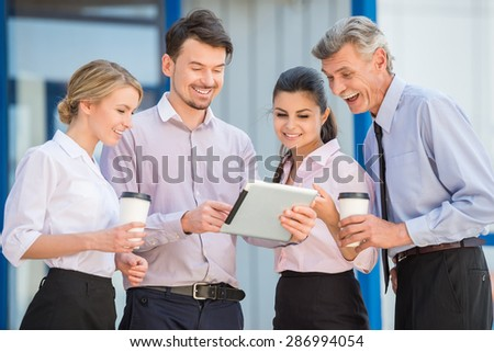 Group of successful office workers having coffee break. Office background.