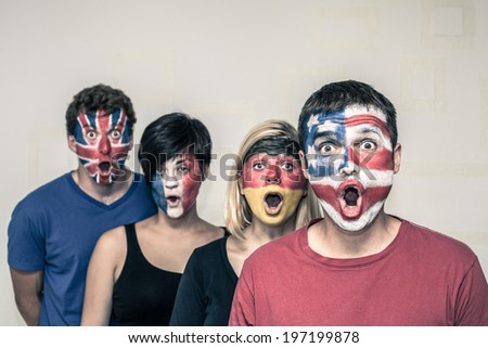 Group of surprised people with painted flags on their faces.