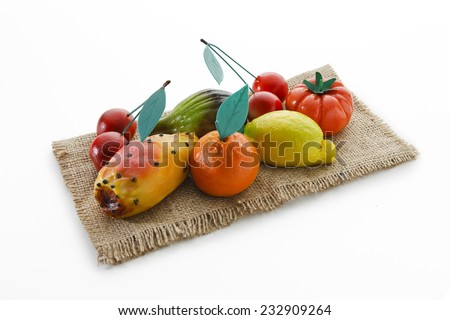 Group of sweet marzipan almond fruit on a jute hanky on withe background. - stock photo