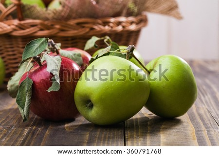 Group of tasty fresh ripe juicy red and green apples with leaves on stalks near wicker basket decorated with burlap on wooden table on white wall background, horizontal photo - stock photo