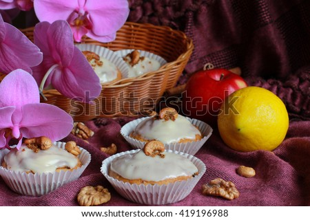 Group of tasty homemade carrot cupcakes (muffins, cakes, pie) decorated with cream cheese, cashews and walnuts, cinnamon sticks, red apple, lemon and pink orchid flower on soft blurred background - stock photo