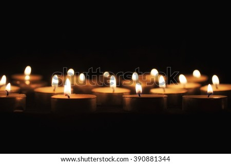 Group of tea candles on a black background - stock photo