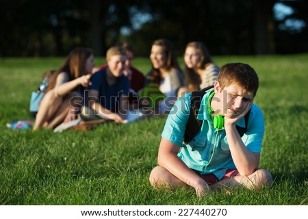Group of teen bullying sad student sitting outdoors - stock photo