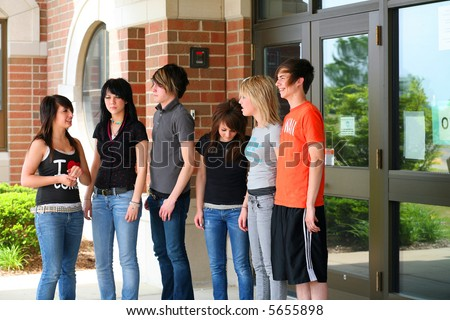 group of teen guys and girls outside of school entrance