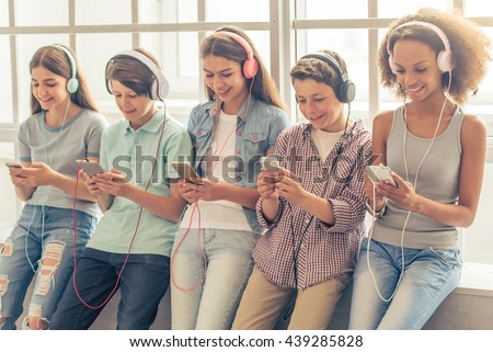 Group of teenage boys and girls in headphones is listening to music using smartphones while sitting against window - stock photo