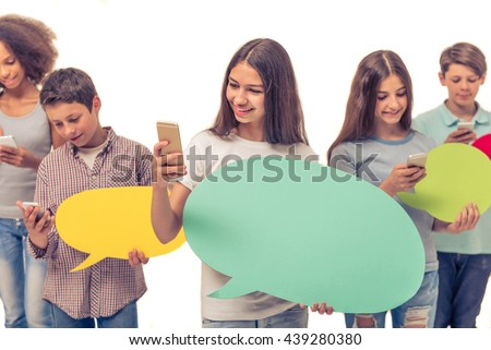 Group of teenage boys and girls is holding speech bubbles, using smartphones and smiling, isolated on white - stock photo