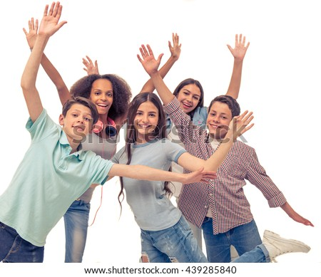 Group of teenage boys and girls is keeping hands up, looking at camera and smiling, isolated on white