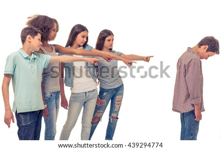 Group of teenage boys and girls is pointing on another boy, who is standing with bent head, isolated on white - stock photo